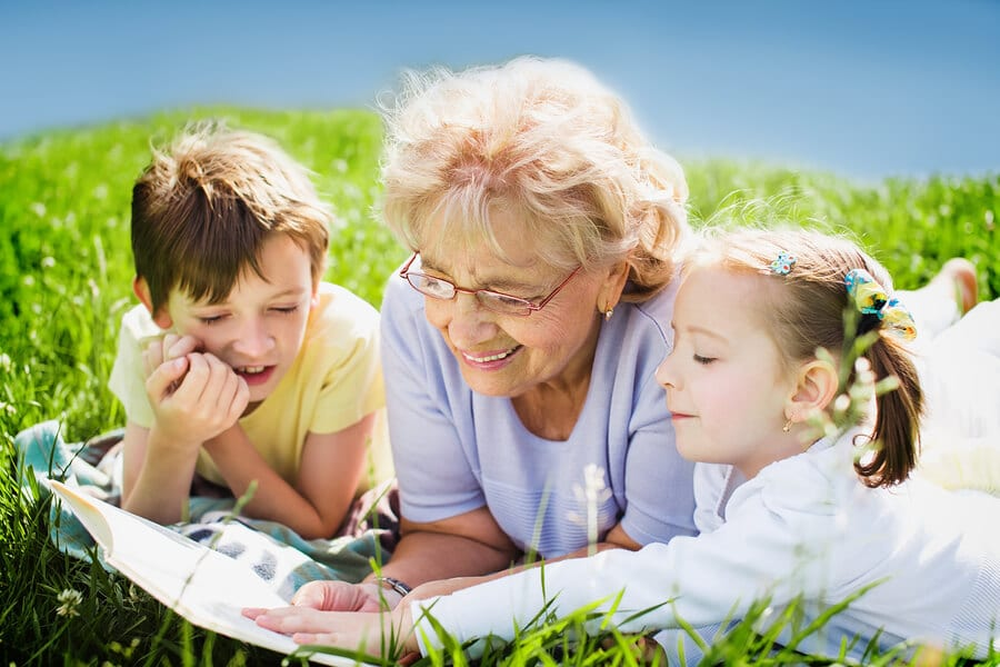grandmother reading a book to her grandchildren