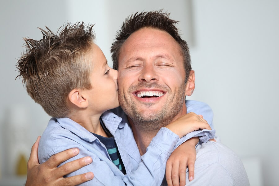 boy kissing his father