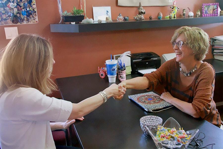 Susan Sandys shaking a clients hand
